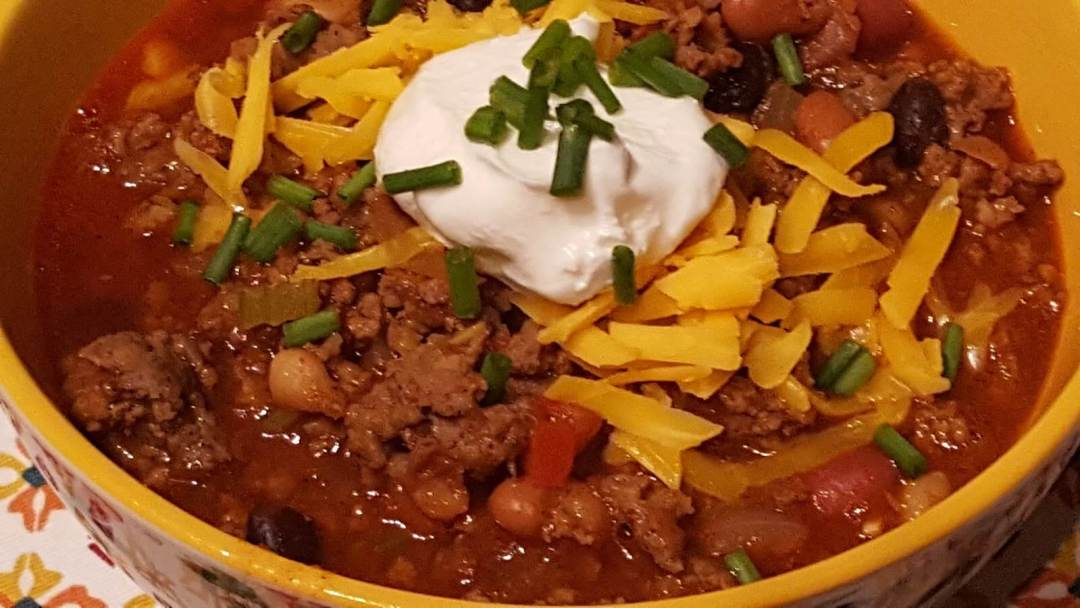 Bowl of Chili with sour cream and shredded cheese with chives on top