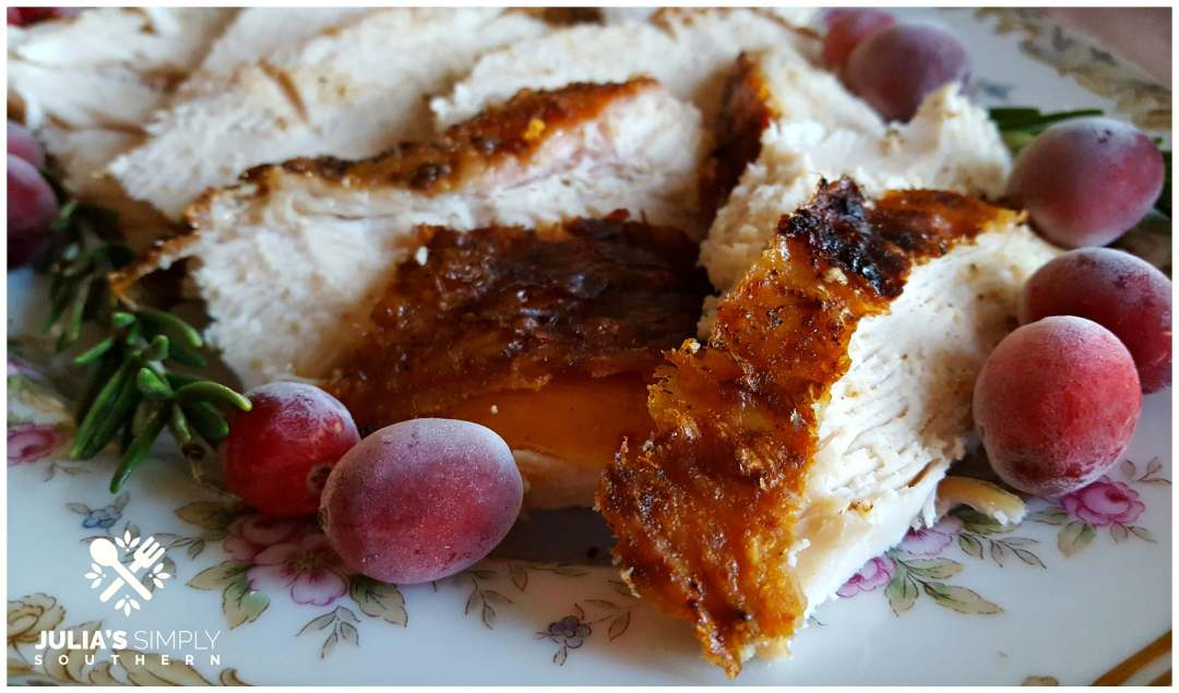 Sliced turkey breast with beautiful browned skin and garnished with fresh cranberries and rosemary