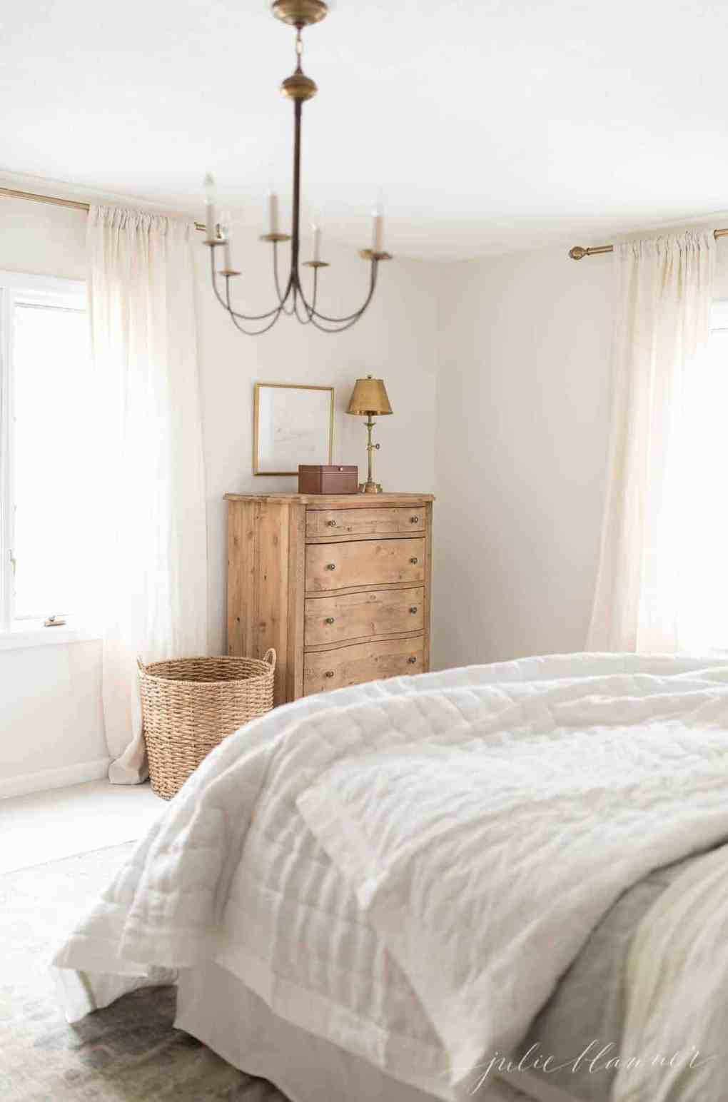 A white bedroom with wooden furniture and a brass chandelier