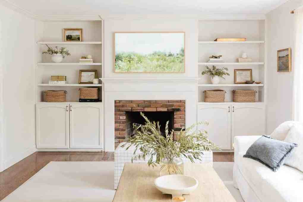 A white living room with bookshelf decor.a brick fireplace surrounded by built ins,