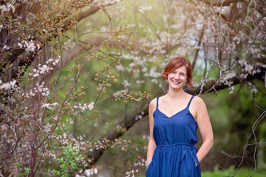 woman in blue dress standing under a blossom tree at the Dominion Arboretum in Ottawa