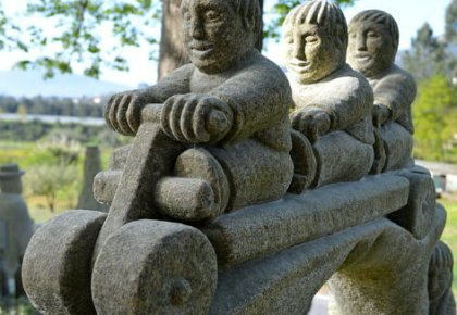 Stone sculpture of three boys on a toy buggy