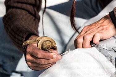 Matelot répare une voile.