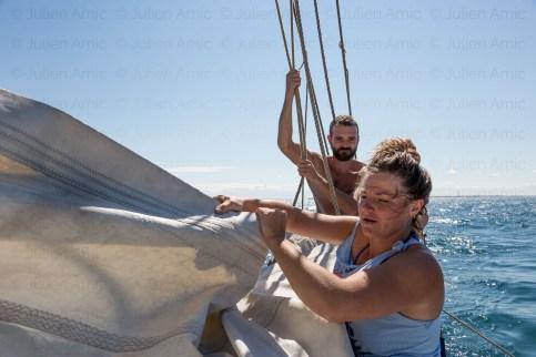 Deux matelots en train de ferler la grand voile.