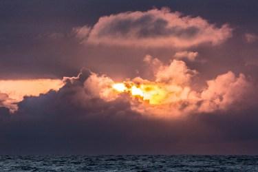 Le soleil se couche entre les nuages au milieu de l'Atlantique