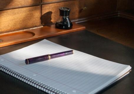 purple fountain pen on blank notebook