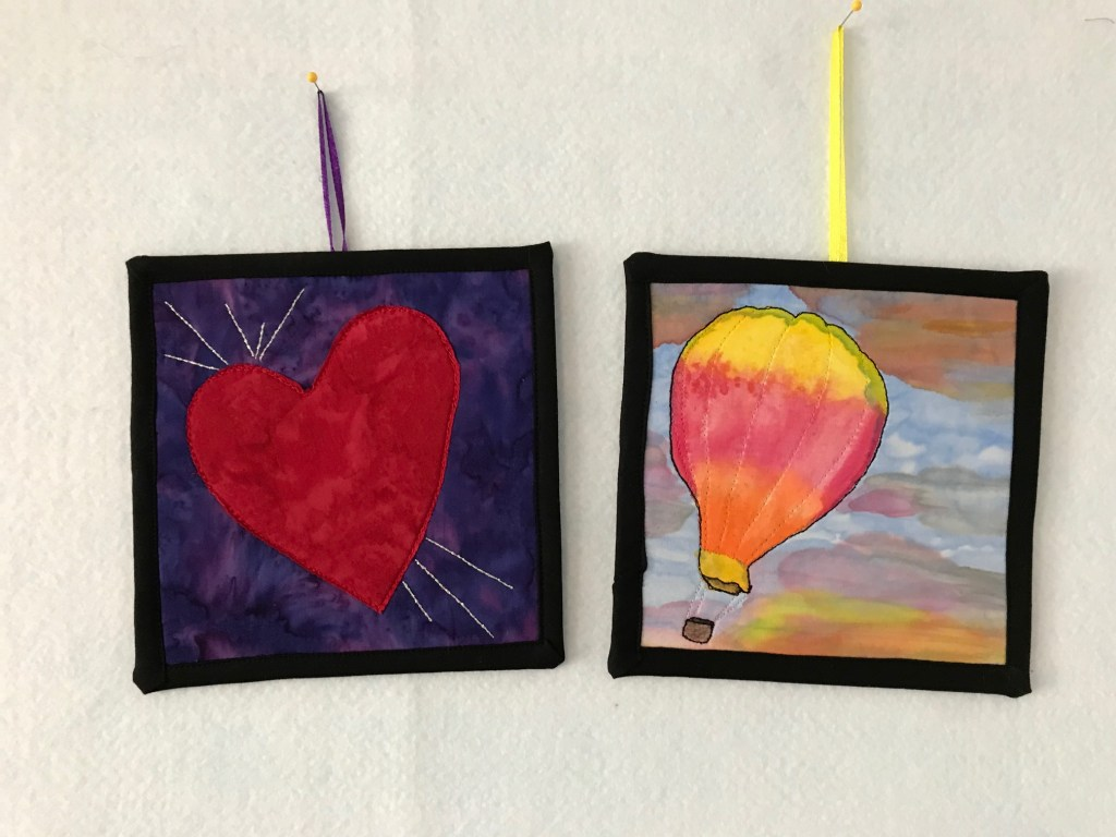 Two small quilted art pieces representing joy. One has a red heart on a purple background and silver lines of stitches. The other is an inked image of a hot air balloon in a sunrise sky.