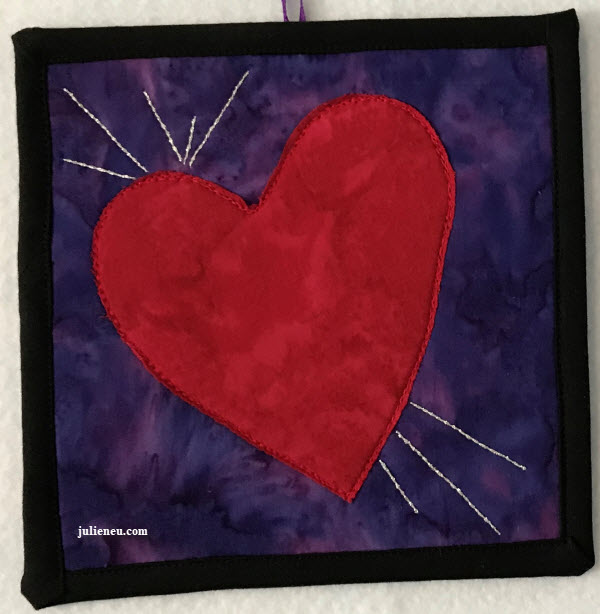 """Small quilted art piece reflecting """"joy"""". Red heart on purple background with silver thread lines emanating from heart on left lobe and bottom."""