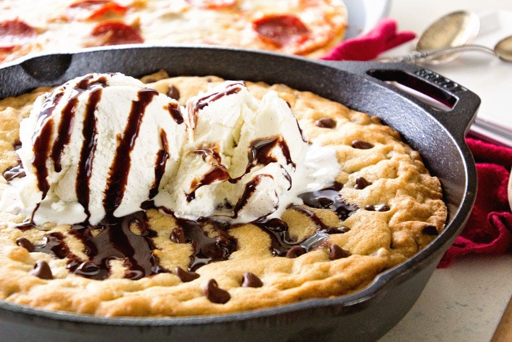 Chocolate Chip Skillet Cookie topped with ice cream and drizzles of chocolate.