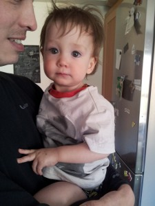 Slightly sombre baby looks at camera, wearing pink Belle and Sebastian T-shirt