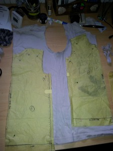 Yellow tissue-paper pattern pieces for front and back of toddler T-shirt laid out on dismantled original adult T-shirt body