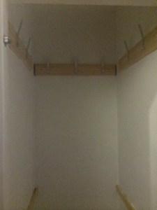 Inside of tall narrow white cupboard, showing coat hooks.