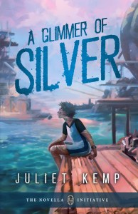 Cover of A Glimmer Of Silver, by Juliet Kemp. An androgynous person with brown skin and short dark hair sits on a dock, with the sea at their feet. They have silver marks on their skin. Behind them there are floating buildings in the distance.