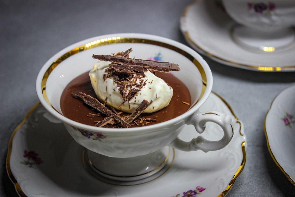 Dieses Bild zeigt eine Porzellantasse mit Goldrand und Blüten gefüllt mit einem frisch gekochten Schokoladenpudding. Dekoriert ist dieser mit Schlagsahne und Schokoladensplittern.