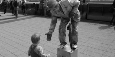 Hier sieht man einen Straßenkünstler, der einem sehr kleinen Jungen die Hand reicht