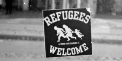 """Hier sieht man einen Aufkleber auf einer Straßenbahnhaltestelle, der Text lautet """"Refugees welcome"""""""