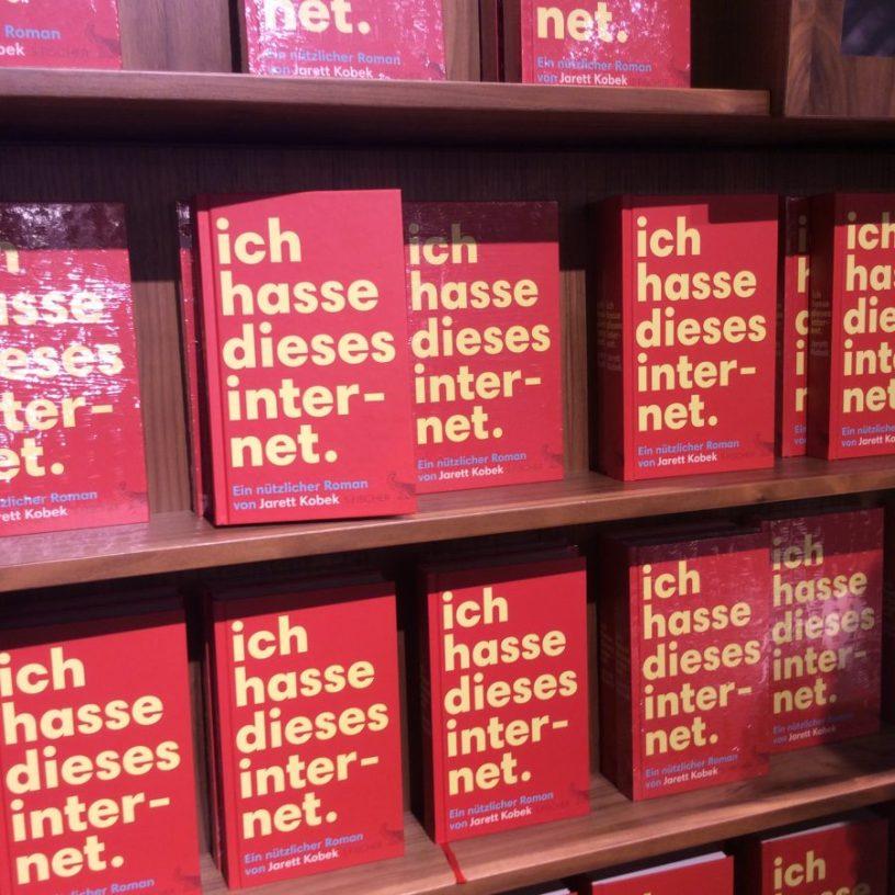 """Hier ist ein Bücherregal mit einem Titel von Jarett Kobek, """"Ich hasse dieses Internet"""". Da der Blogpost ja eigentlich das Gegenteil sagt, entsteht hier eine schöne Text-Bild-Schere."""
