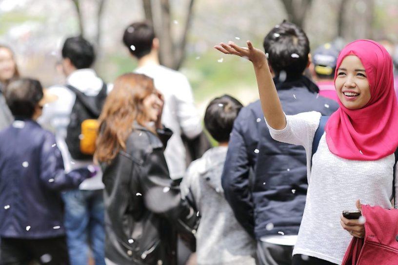 Hier ist ein junges Mädchen mit einer pinkfarbenen Hijab zu sehen. Vom Himmel fällt Schnee, im Hintergrund stehen einige Menschen, von der Kamera abgewandt