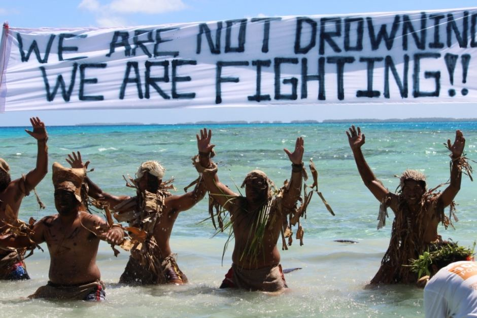 "Protesters in Fiji show strength in the face of rising sea levels with the 350 Pacific slogan – ""We are not drowning, we are fighting."""