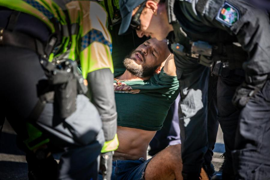 Police detain an Extinction Rebellion protester at Queensland's Parliament House.