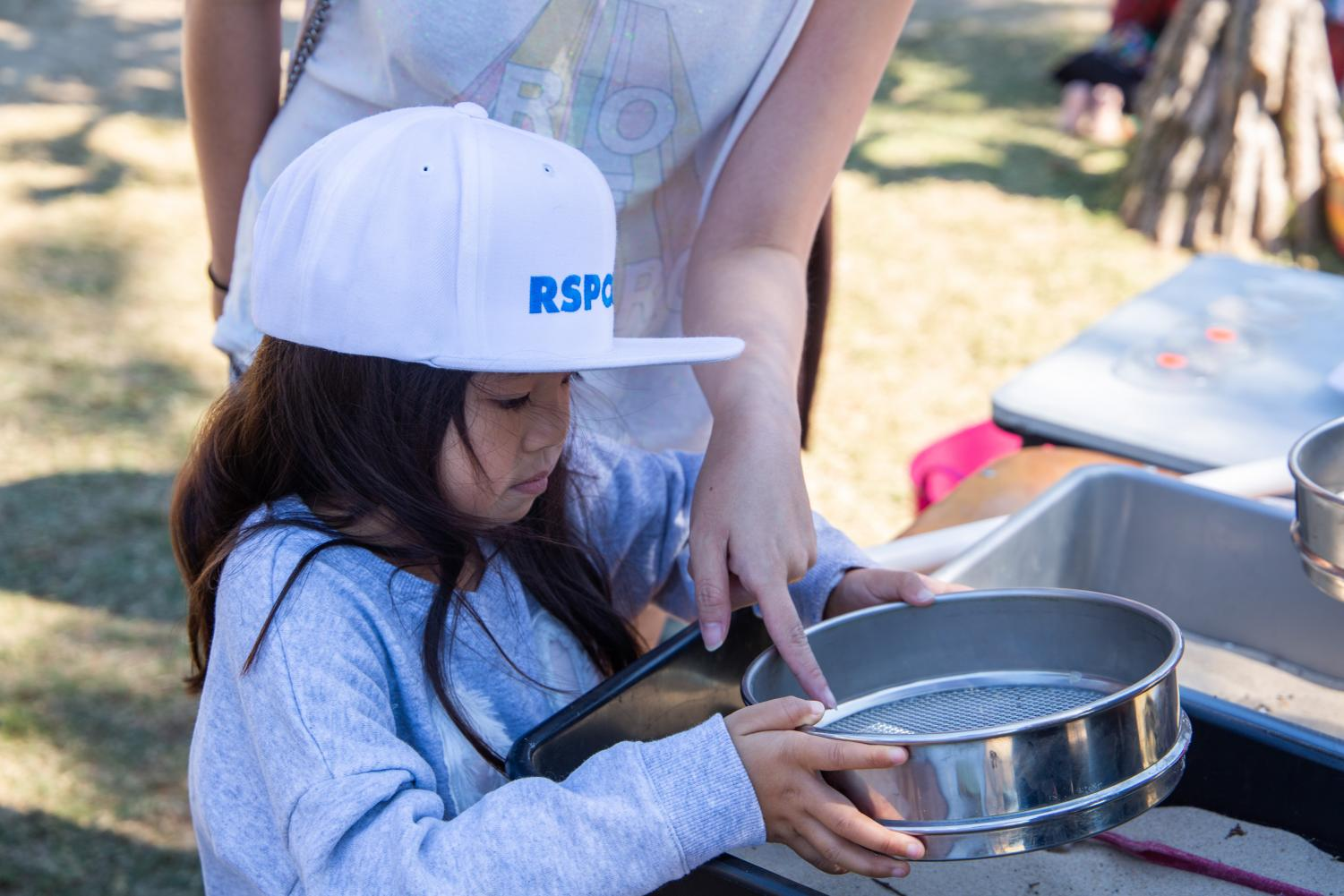 Child being shown how to sift micro plastics from sand with a sieve
