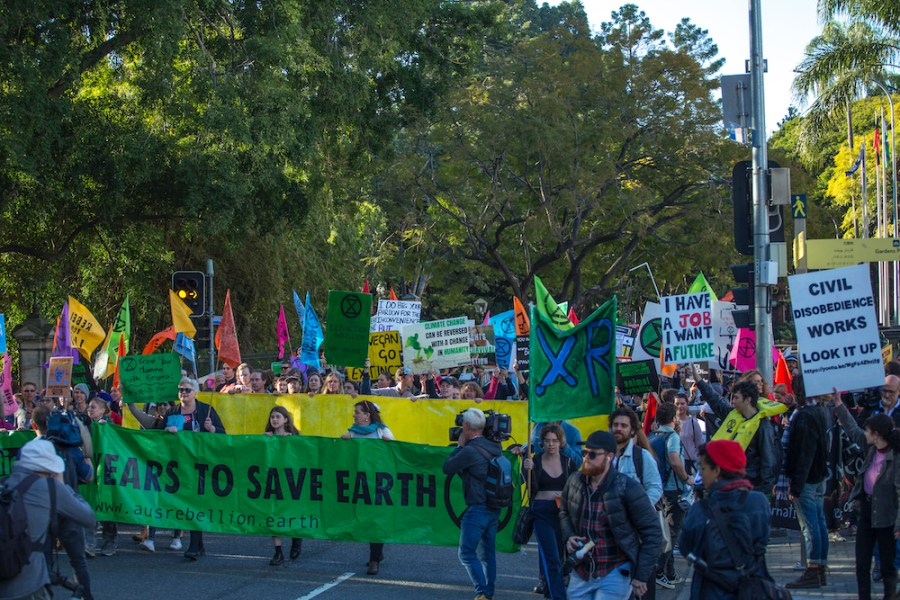 Extinction+Rebellion+protesters+outside+Queensland+Parliament+House+marching+behind+a+large+banner