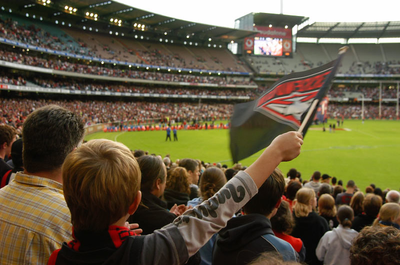 Supporters cheer on Essendon at an AFL match. Photo: Hunter Nield (CC BY-SA 2.0)