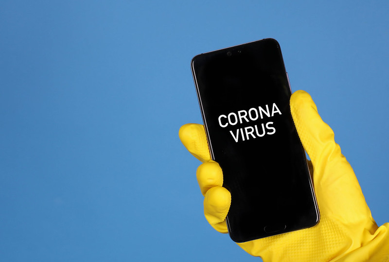 Hands in yellow rubber gloves holding mobile phone with Coronavirus text. Photo: Marco Verch (CC BY 2.0)