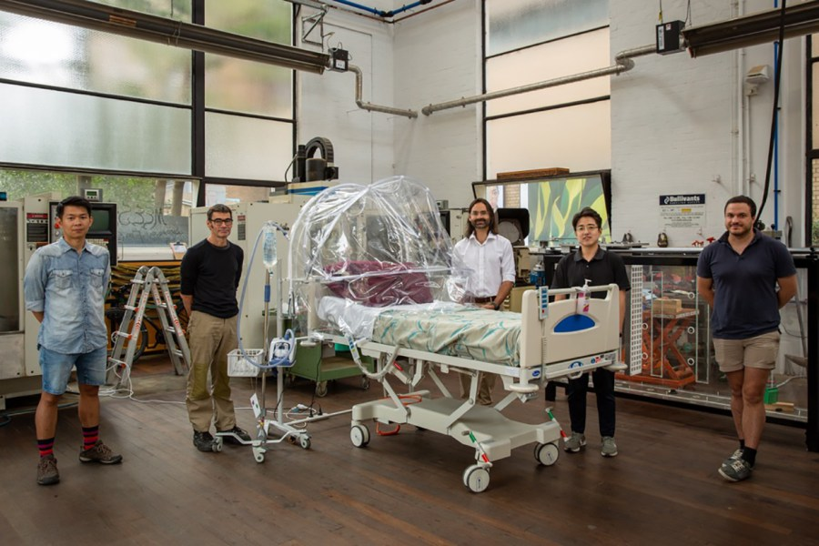 Dr Jason Monty (pictured centre) with his University of Melbourne team of engineers and prototype ventilation hood, which is being trialled in nine Victorian hospitals and one in the Northern Territory. Photo: supplied.