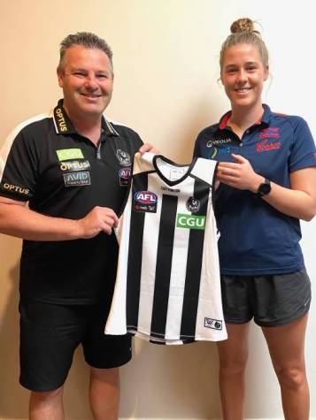 Collingwood AFLW coach Steve Symonds gives Bella Smith her guernsey after she was drafted to Collingwood in the AFLW Draft.