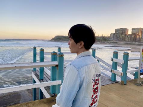 man standing on a pier at a beach
