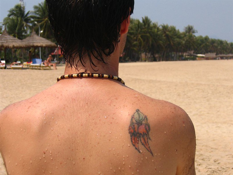 man at a beach with a tattoo on his back