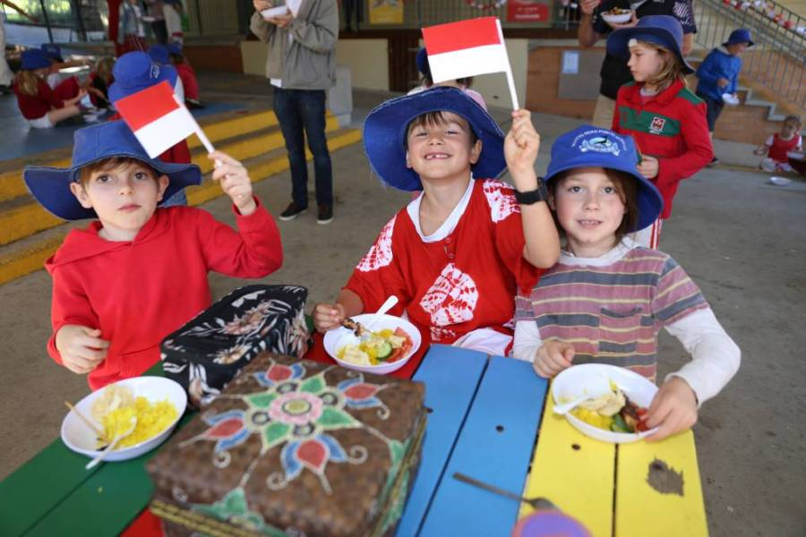 school children waving indonesian flags
