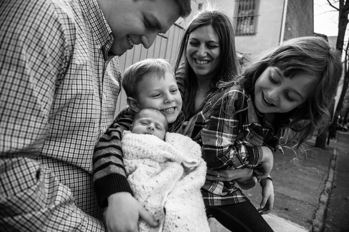 Family cuddling newborn sibling.