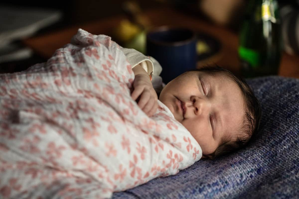 Newborn baby sleeping on blanket.