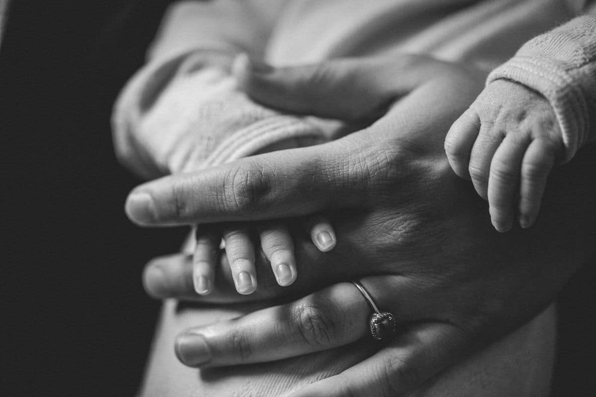 Close up of baby and mother's hands.