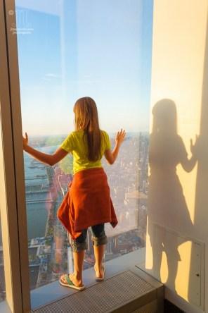 Meine große Tochter lehnt sich gegen eines der großen Fenster des One World Trade Center. https://junghahn24.com/finale-in-new-york/