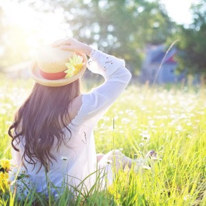 Mental health benefits of being in Nature: Woman wearing a straw hat, sat in a sunny field facing away from the camera