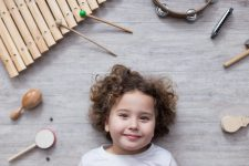 beautiful little girl surrounded by several percussion instruments on a wooden grey table