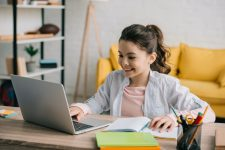 cute smiling child using laptop while sitting at desk with copy books and doing homework
