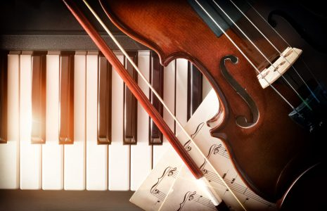 Violin bow and sheet music on piano keys. Concept of interpretation of piano music and string instruments. Top view. Horizontal composition.