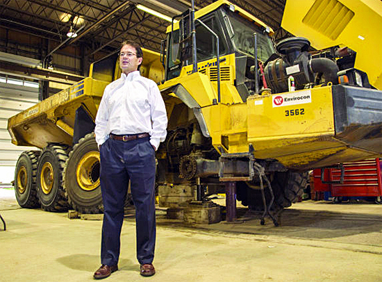 Brian Sheridan, Modern Machinery president, stands next to an articulated truck in Modern Machinery's repair shop in Missoula last week. In addition to the bulldozers, Modern is currently working on shipping a dozen substantially larger 240-ton trucks to the gold mine project. The trucks have tires that are 12 feet in diameter.