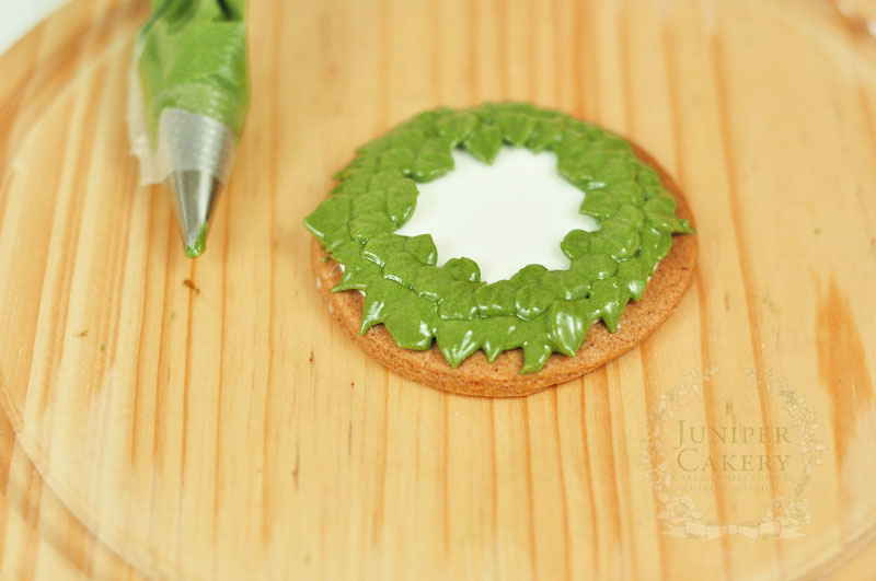 Piping Christmas wreath cookies by Juniper Cakery