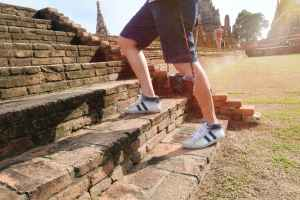 person wearing white and black mid rise sneakers at borobudur indonesia