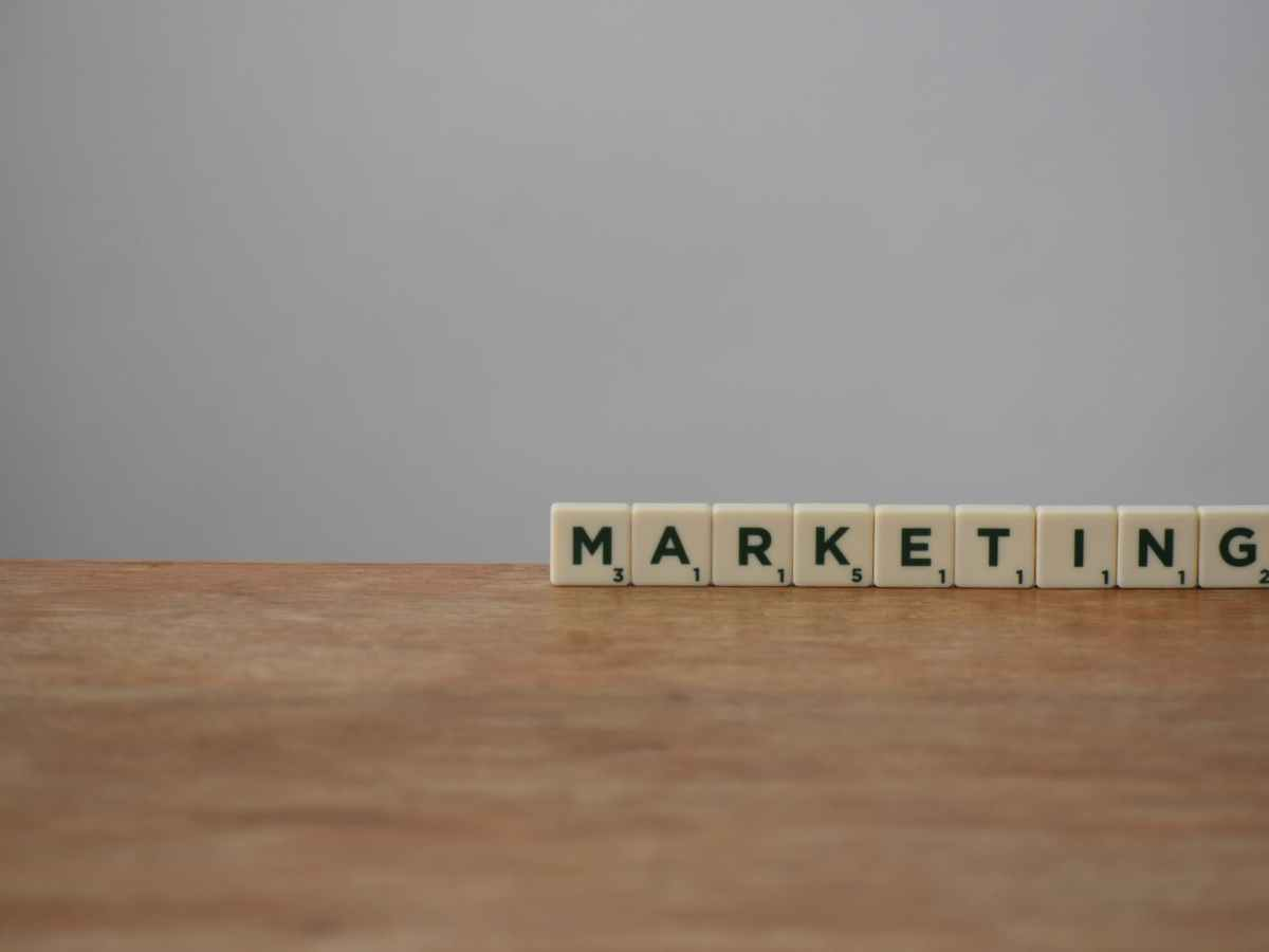 white and black marketing word on brown wooden table