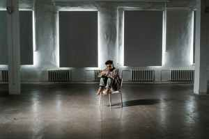 a frightened man sitting alone on a chair