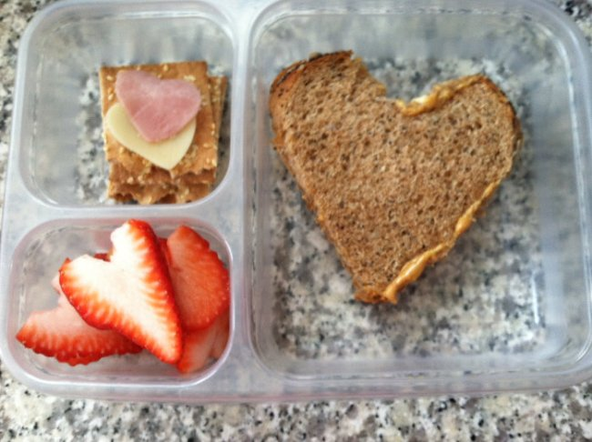Peanut butter and honey sandwich, Ak-Mak crackers with heart shaped ham and cheese, and heart shaped strawberries