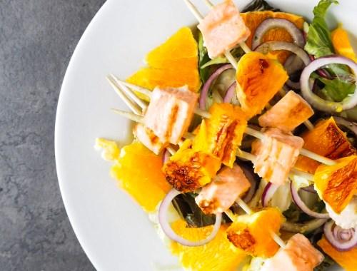 Orangen-Lachsspieße auf Teller