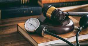 Judge gavel and a blood pressure gauge on a wooden desk