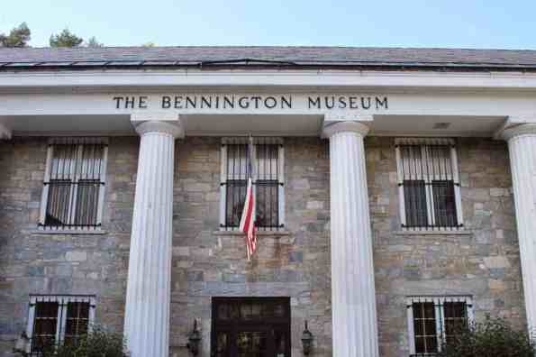 Photograph of the front of Bennington Museum - a two-story stone building with white pillars and bars on the windows.